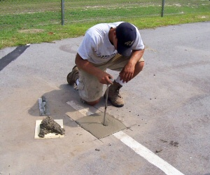 Positioning anchor in wet concrete and trowel to grade.